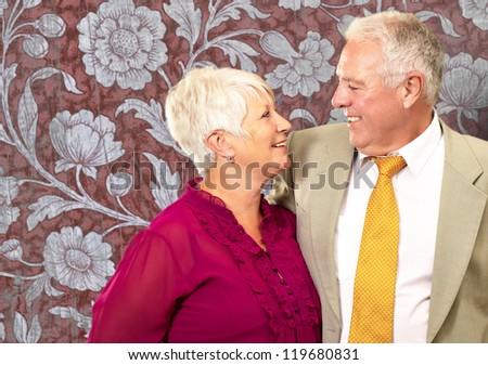 Portrait Of A Happy Senior Couple On Wallpaper Background - stock photo