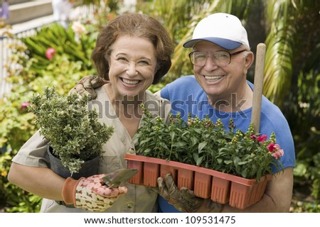 Portrait of a happy senior couple working in their own garden - stock photo