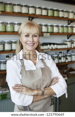 Portrait of a happy senior employee with arms crossed in spice store - stock photo