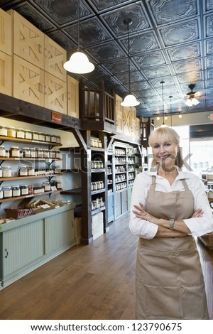 Portrait of a happy senior female spice merchant standing with arms crossed in store