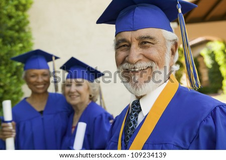 Portrait of a happy senior male graduate with female friends in background - stock photo
