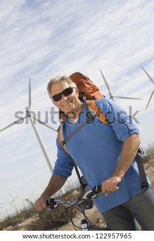 Portrait of a happy senior male tourist standing with bicycle and backpack at wind farm - stock photo