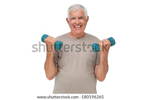 Portrait of a happy senior man exercising with dumbbells over white background