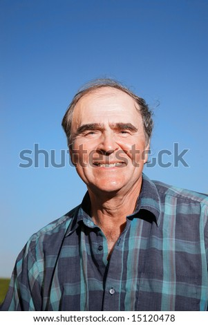 Portrait of a happy senior man outdoors over blue sky. - stock photo
