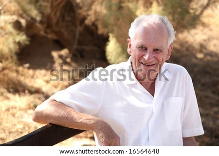 Portrait of a happy senior man relaxing outdoors - stock photo