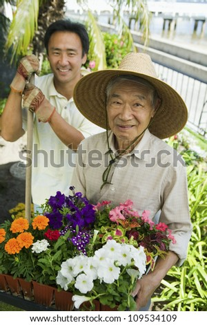 Portrait of a happy senior man with son gardening together