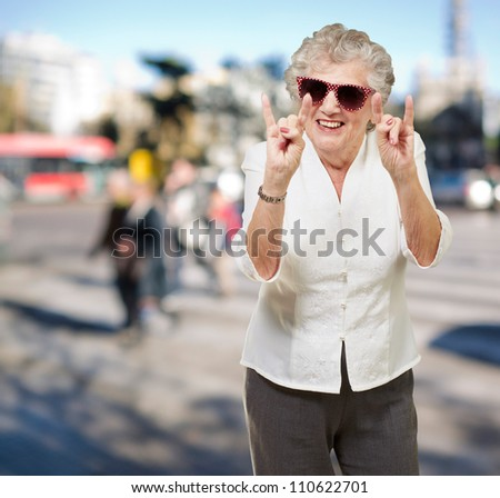 portrait of a happy senior woman doing rock symbol at crowded street - stock photo