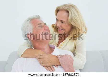 Portrait of a happy senior woman embracing man from behind at home