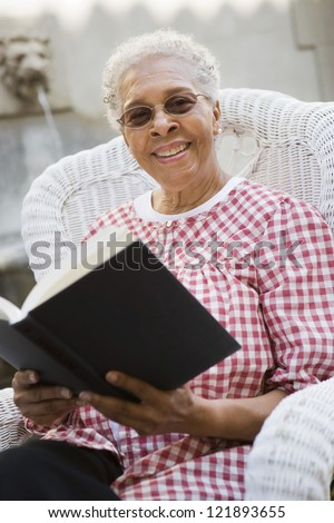 Portrait of a happy senior woman holding book - stock photo
