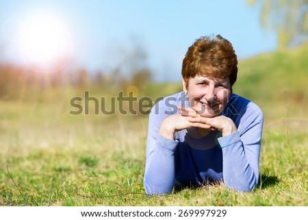 Portrait of a happy senior woman on field - stock photo