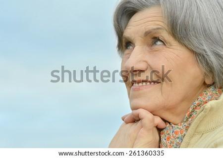 Portrait of a happy senior woman outdoors - stock photo