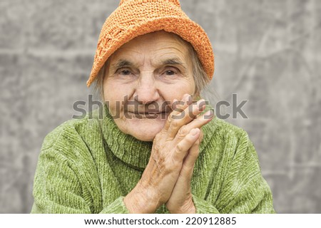 Portrait of a happy senior woman smiling at the camera - stock photo