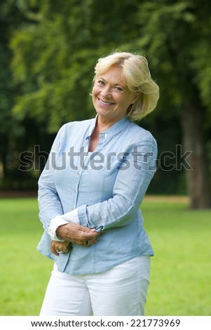 Portrait of a happy senior woman smiling in the park - stock photo
