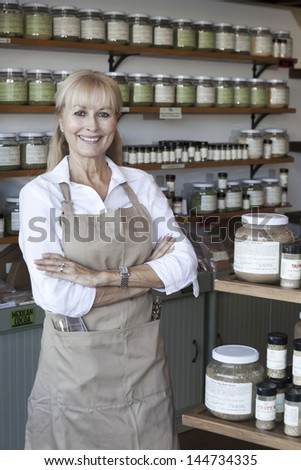 Portrait of a happy senior woman with arms crossed in spice store - stock photo