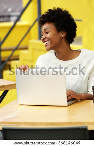 Portrait of a happy smiling african woman sitting at outdoor cafe with a laptop
