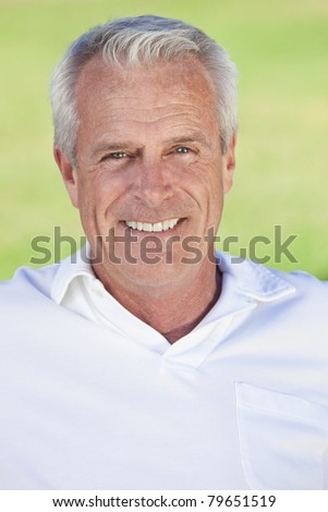Portrait of a happy smiling attractive handsome senior man with a natural green background - stock photo