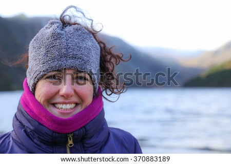 Portrait of a happy smiling beautiful woman wearing colorful warm winter clothes with a red face from the cold standing in mountain landscape in Ireland - stock photo