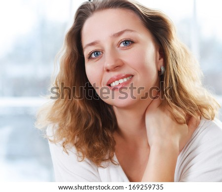 Portrait of a happy smiling blond woman near the window
