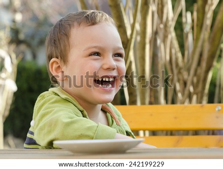 Portrait of a happy smiling child at a garden table  - stock photo