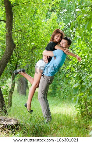 Portrait of a Happy smiling couple: handsome young man holding beautiful young woman outdoors on a bright sunny day of spring or summer on the green garden or park background