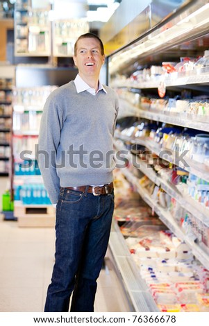 Portrait of a happy smiling customer in a grocery store - stock photo