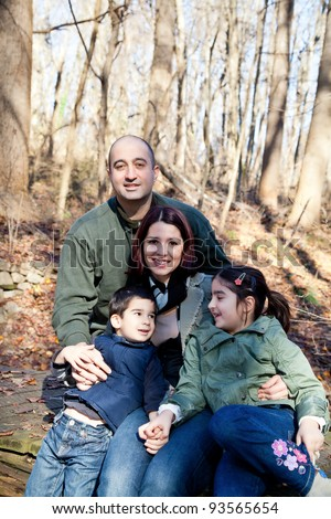 Portrait of a happy smiling family in the forest. Mother and father are looking at the camera and the boy and girl are making eye contact looking at each other.