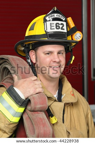 portrait of a happy smiling firefighter standing in front of fire engine in uniform holding a fire hose - stock photo