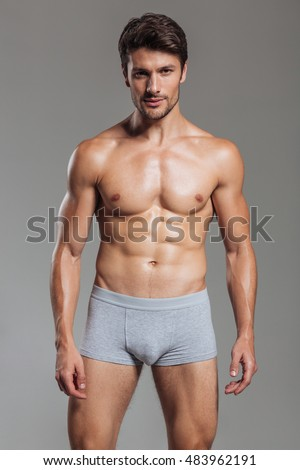 Portrait of a happy smiling muscular man in underwear standing isolated on a gray background
