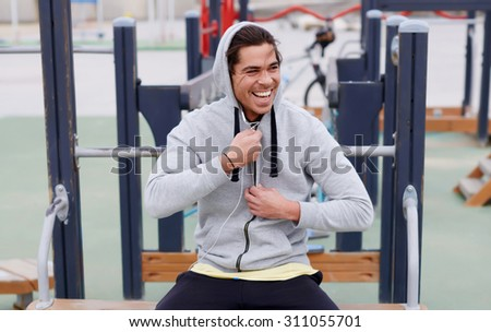 Portrait of a happy smiling sportsman having a break after workout outdoors, jogger man listening to music in headphones enjoying rest,young sporty guy resting after training sitting on sports ground  - stock photo
