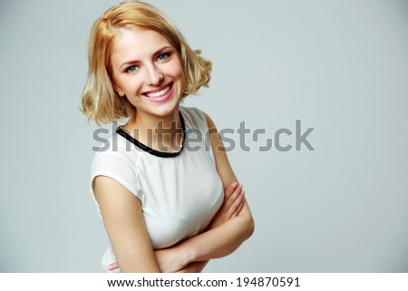 Portrait of a happy smiling woman with arms folded on gray background - stock photo