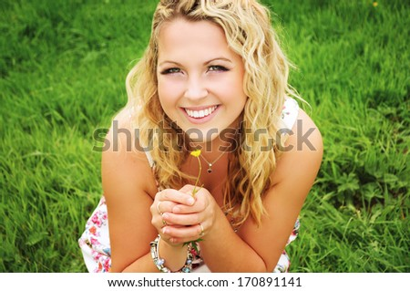Portrait of a happy smiling young blonde woman on a green field holding a tiny yellow flower.