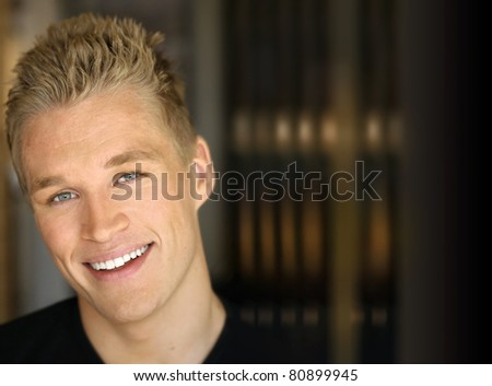 Portrait of a happy smiling young man against dark modern background - stock photo