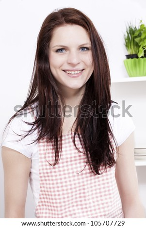 portrait of a happy smiling young woman in kitchen - stock photo
