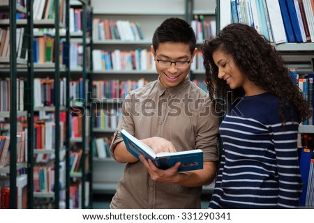 Portrait of a happy students searching book in library together - stock photo
