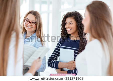 Portrait of a happy students speaking in the university hall - stock photo