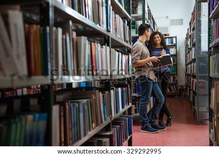 Portrait of a happy students talking in library  - stock photo