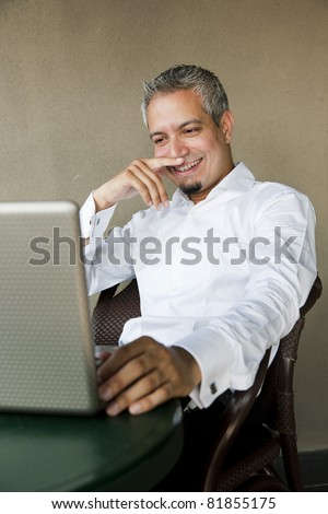 portrait of a happy successful businessman with grey hair working on the laptop, Indian muslim businessman working. - stock photo