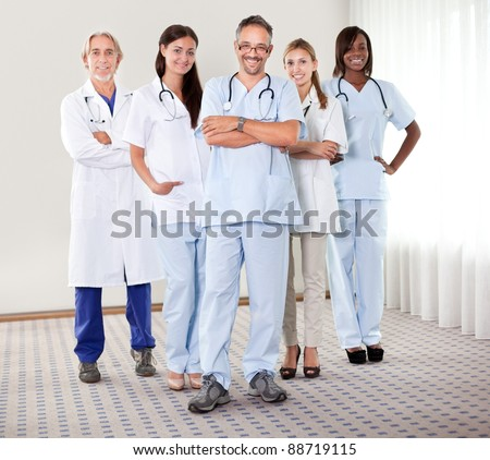 Portrait of a happy successful group of doctors with folded hands