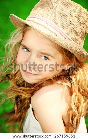 Portrait of a happy summer girl in straw hat. Happy childhood. Countryside. - stock photo