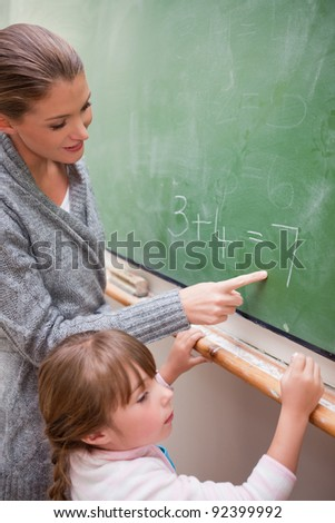 Portrait of a happy teacher and a pupil making an addition on a blackboard - stock photo