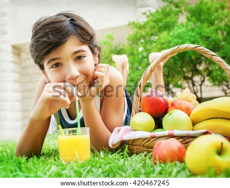 Portrait of a happy teen boy lying down on fresh green grass field and drinking tasty juice, eating fruits, enjoying healthy nutrition in the summer camp - stock photo