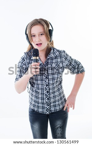 portrait of a happy teen little singing girl with microphone in headphones, isolated on white background. Beautiful blond singing music girl - stock photo
