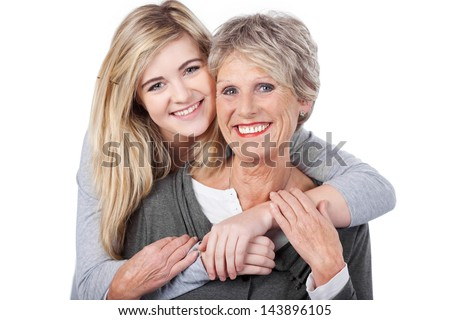 Portrait of a happy teenage girl embracing grandmother from behind against white background - stock photo