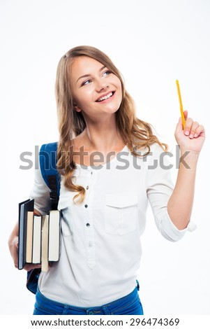 Portrait of a happy thoughtful girl with backpack holding books and pencil. Looking up - stock photo
