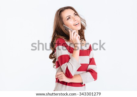 Portrait of a happy thoughtful woman talking on the phone and looking up at copyspace isolated on a white background - stock photo