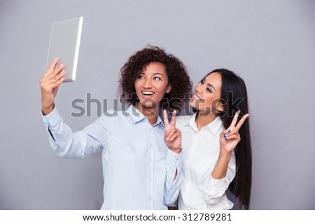 Portrait of a happy two girls making selfie photo on tablet computer while showing two fingers sign on gray background - stock photo