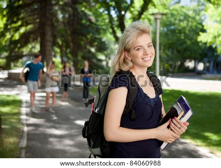 Portrait of a happy university girl walking to class outdoors - stock photo