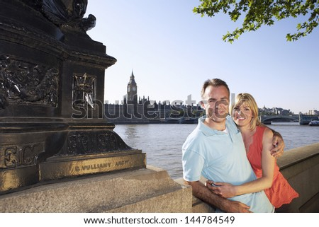 Portrait of a happy vacationing couple standing against Thames River - stock photo
