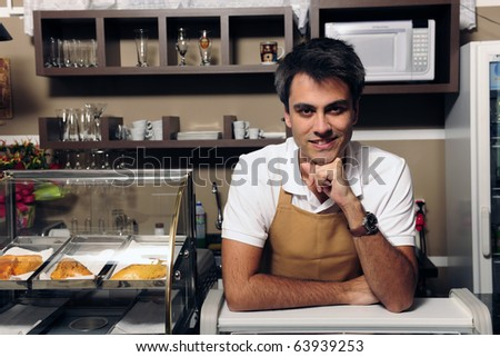 portrait of a happy waiter or owner at the cafe - stock photo