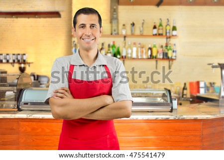 portrait of a happy waiter with crossed arms standing at his coffee bar